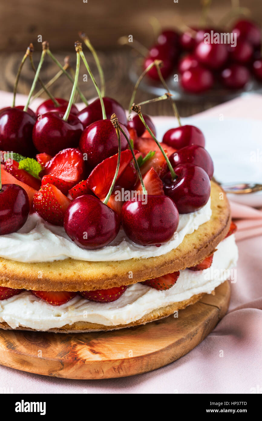 Homemade cream layer cake, fresh, colorful, and delicious dessert with juicy strawberries, sweet cherry, and whipped - Stock Image