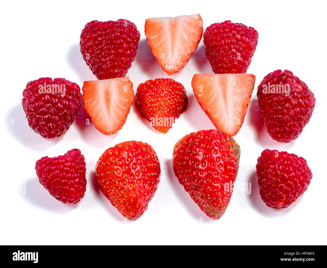 Chopped starwberries and raspberries making a pattern on a white background - Stock Image