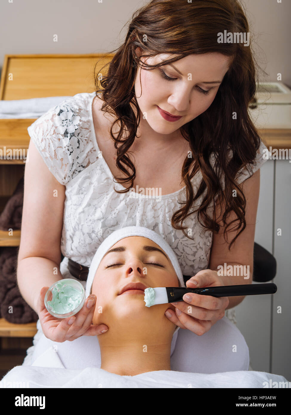 Photo of a young woman getting a facial in a salon. - Stock Image