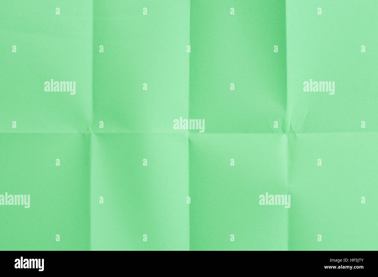 Green sheet of paper folded in eight parts - Stock Image