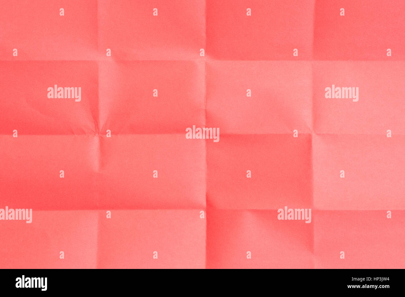 Red sheet of paper folded many times - Stock Image
