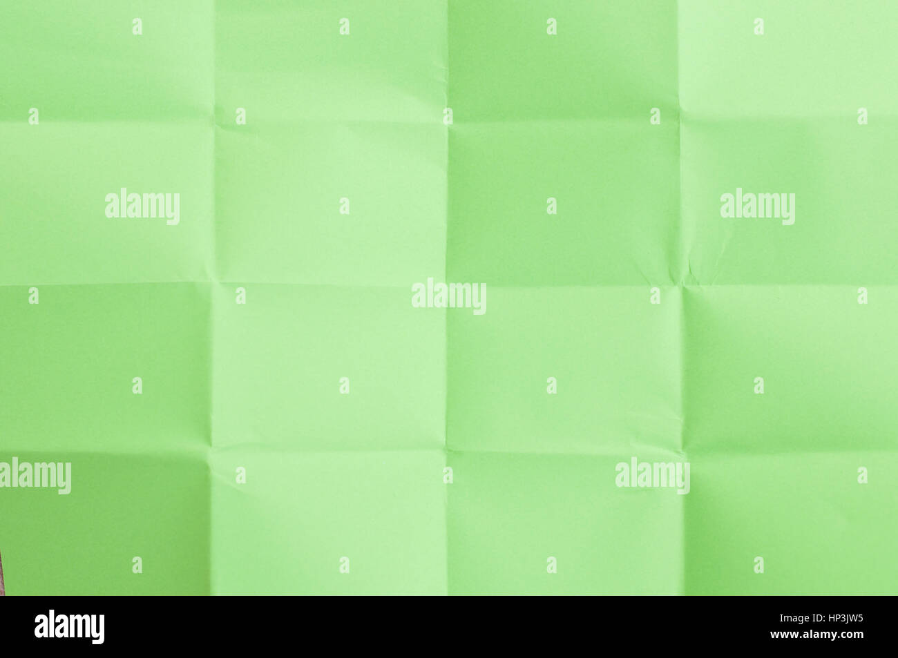 Green sheet of paper folded in sixteen parts - Stock Image