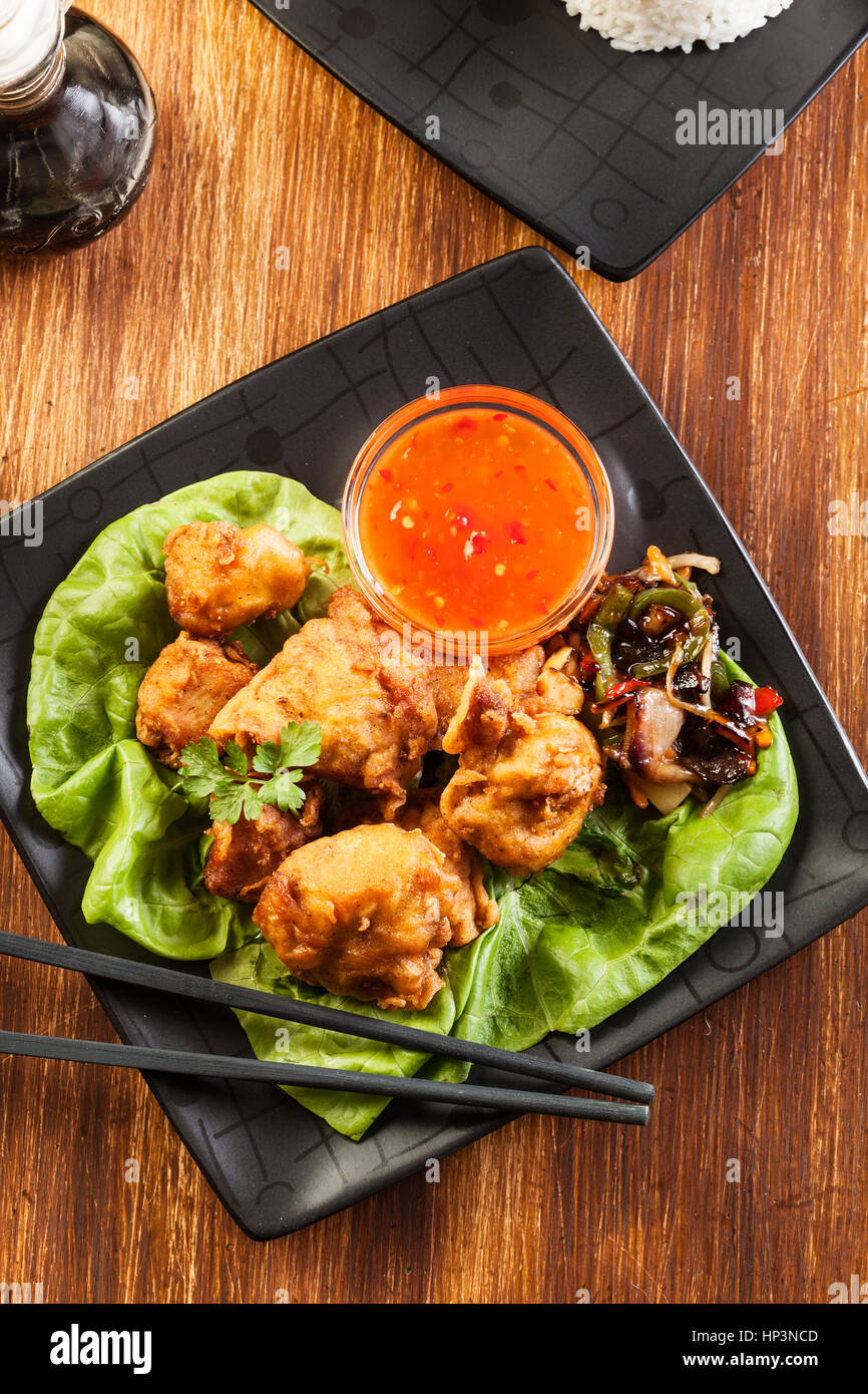 Fried chicken pieces in batter on a plate - Stock Image