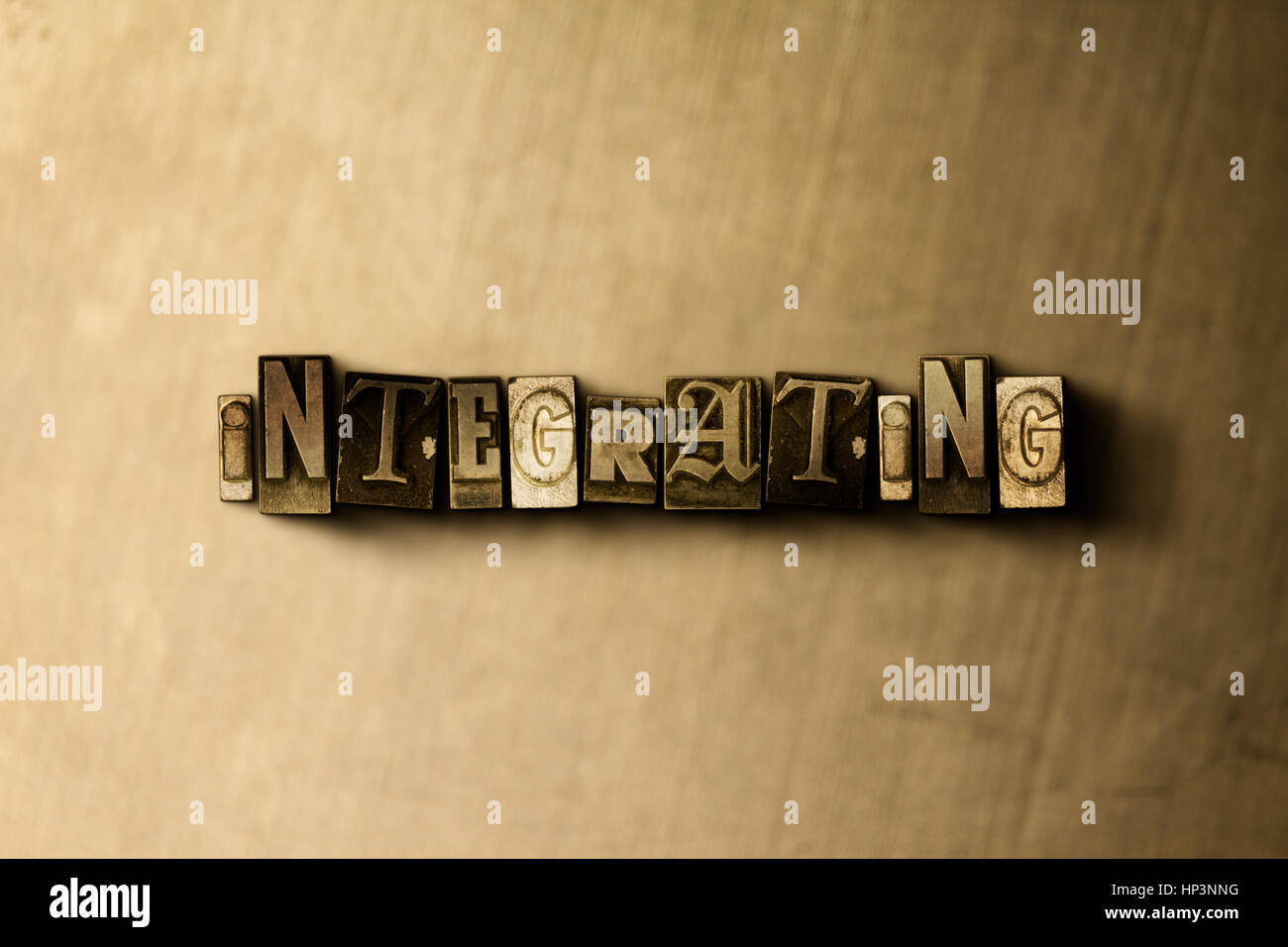 INTEGRATING - close-up of grungy vintage typeset word on metal backdrop. Royalty free stock illustration.  Can be - Stock Image