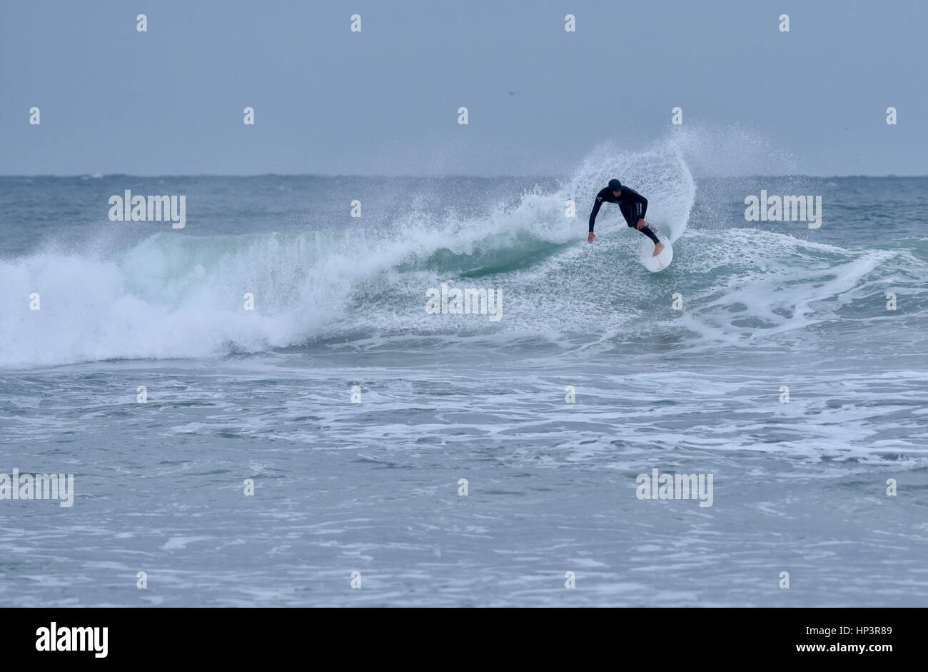 Surfer on wave despite severe weather, high surf and waves crash upon shore of Mission Beach, San Diego,  California. Stock Photo