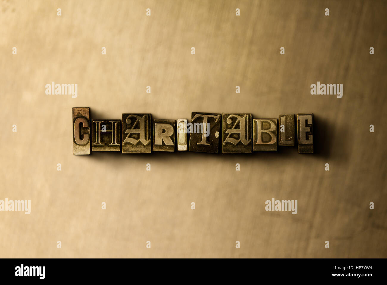 CHARITABLE - close-up of grungy vintage typeset word on metal backdrop. Royalty free stock illustration.  Can be - Stock Image