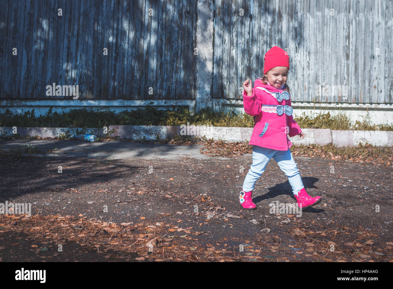 Little girl in a pink coat, jeans and pink boots walking in the park. - Stock Image