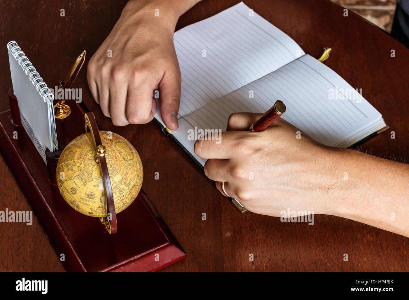 man writes with his left hand in the diary entries. left-handed - Stock Image