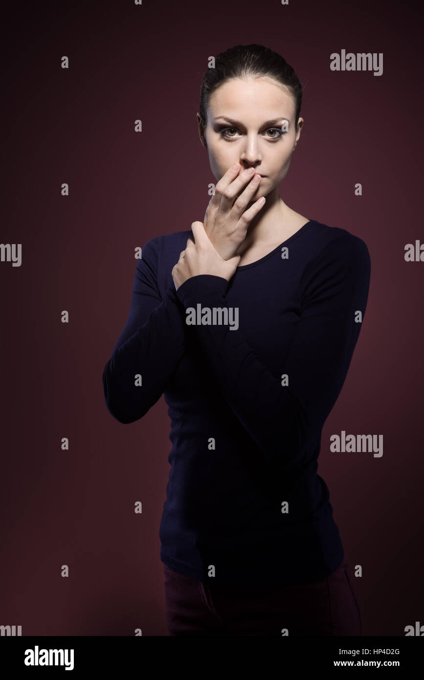 Scared woman staring at camera on dark background - Stock Image