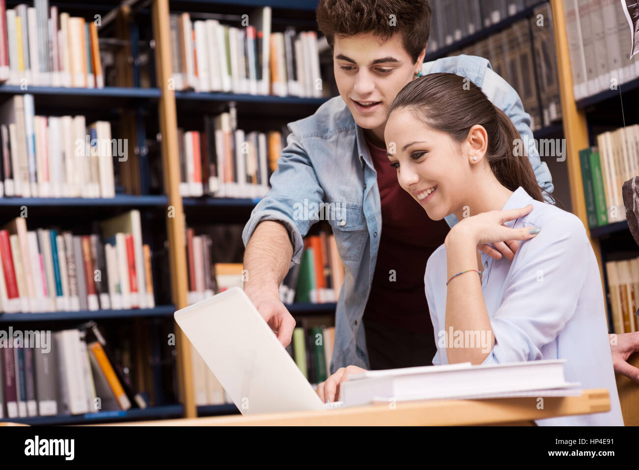 Schoolmates studying together at the library with bookshelves on background - Stock Image