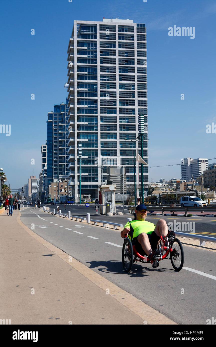 middle aged man riding recumbent bicycle on sidewalk near to beachfront, tel aviv, israel Stock Photo