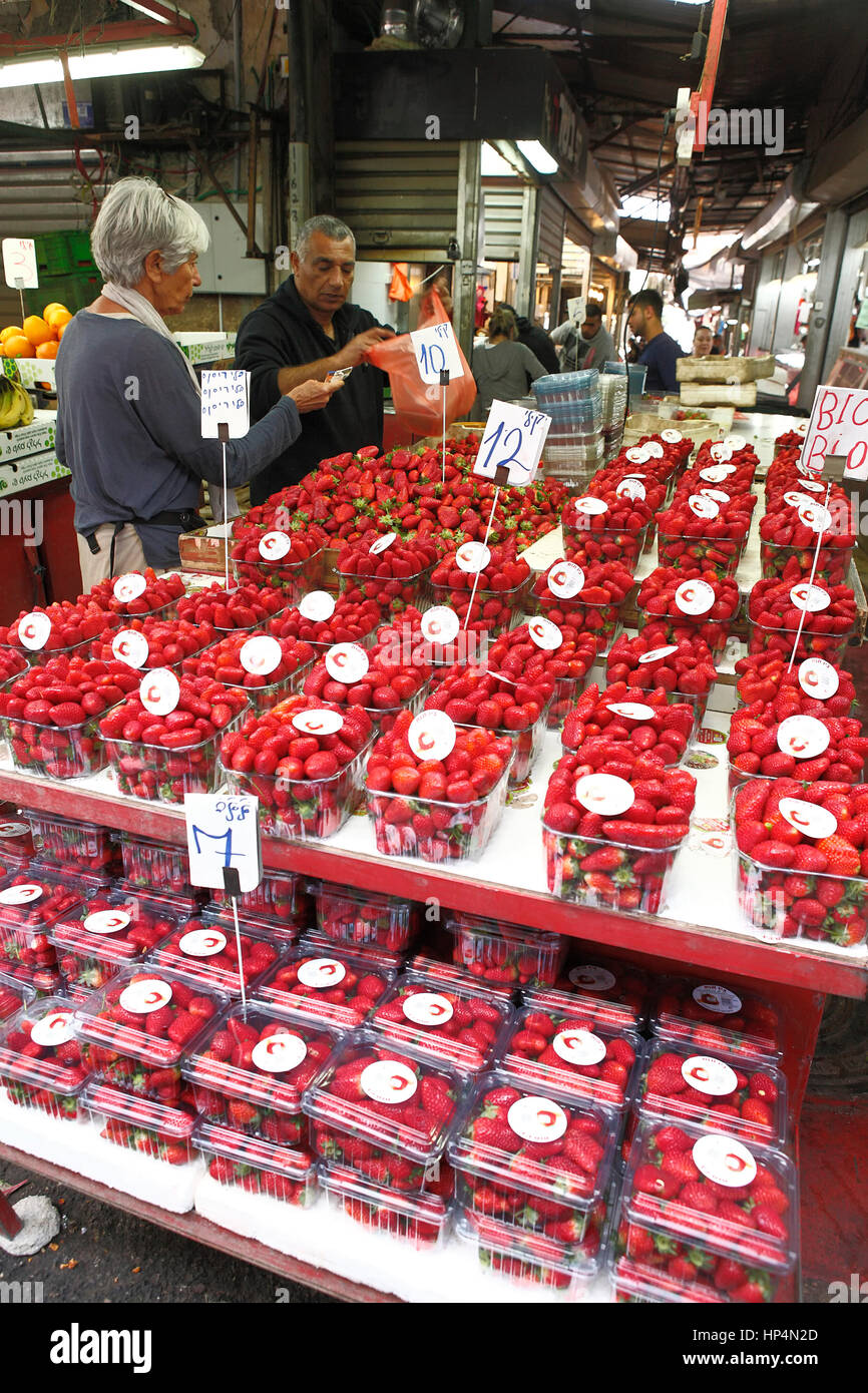 dealer sells fresh israeli strawberries infront of his shop at carmel market, tel aviv, israel Stock Photo