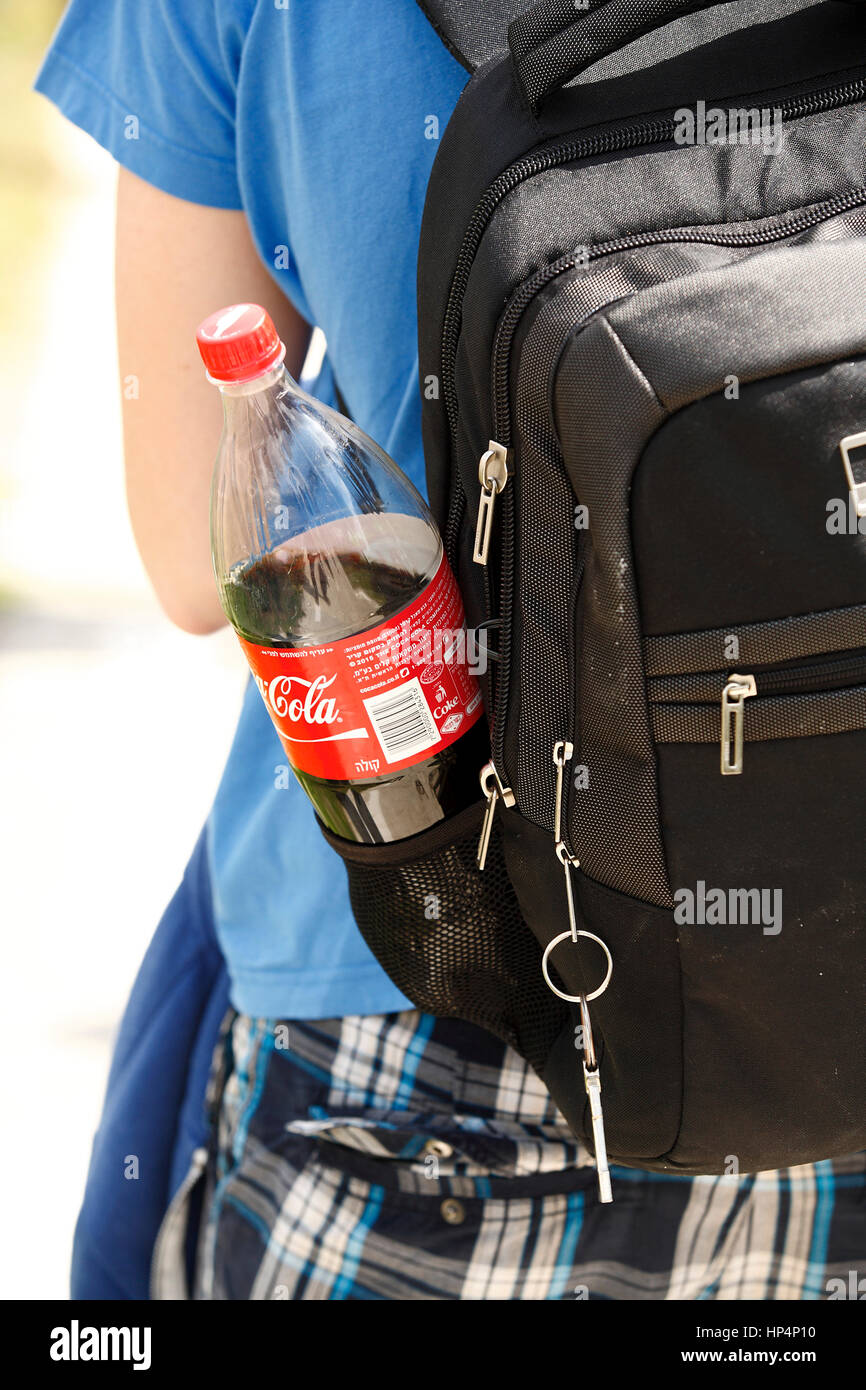 close up softdrink plastic bottle attached on backpack during city trip, jerusalem, israel Stock Photo