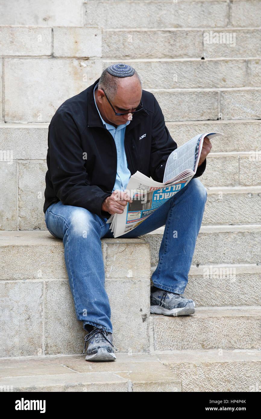 jewish man sitting nearby jaffa gate and reading an newspaper, old city, jerusalem, israel Stock Photo