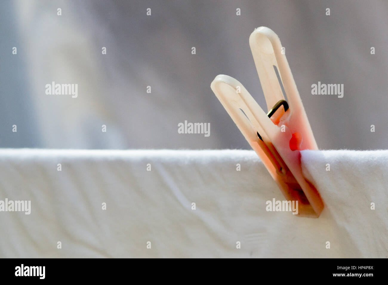 Minimalistic shot of a laundry clip holding a white sheet. Perfect for denoting chores and cleanliness - Stock Image