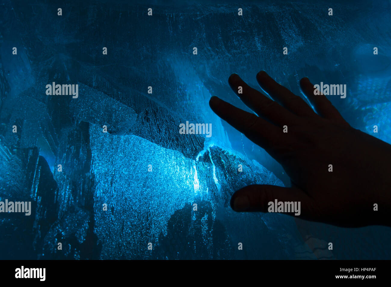 Hand on a cold blue ice block, the relationship between humans and nature, between people and natural phenomena, - Stock Image