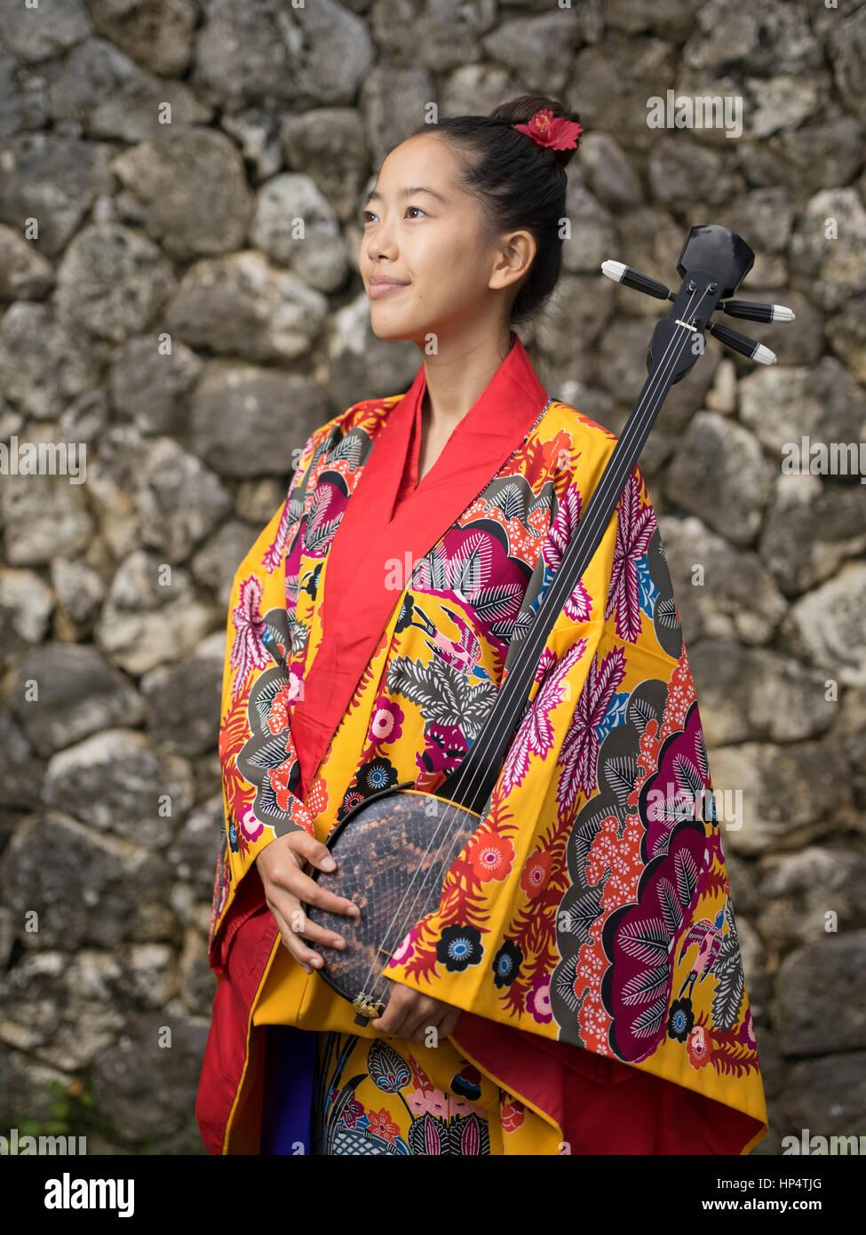 Okinawa musician Nayuta Hirano with sanshin (instrument) and traditional Okinawan ryuso kimono at Murasaki Mura, - Stock Image