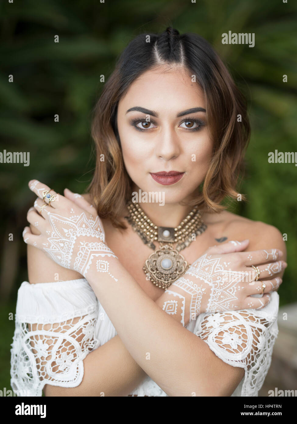 Bohemian woman with white henna on hands - Stock Image