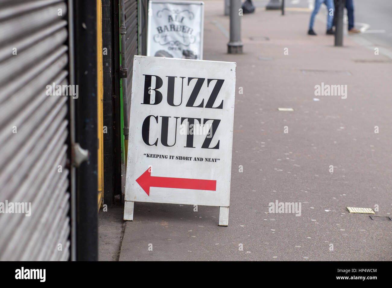 Sign outside men's barbers reading 'Buzz Cutz' - Stock Image