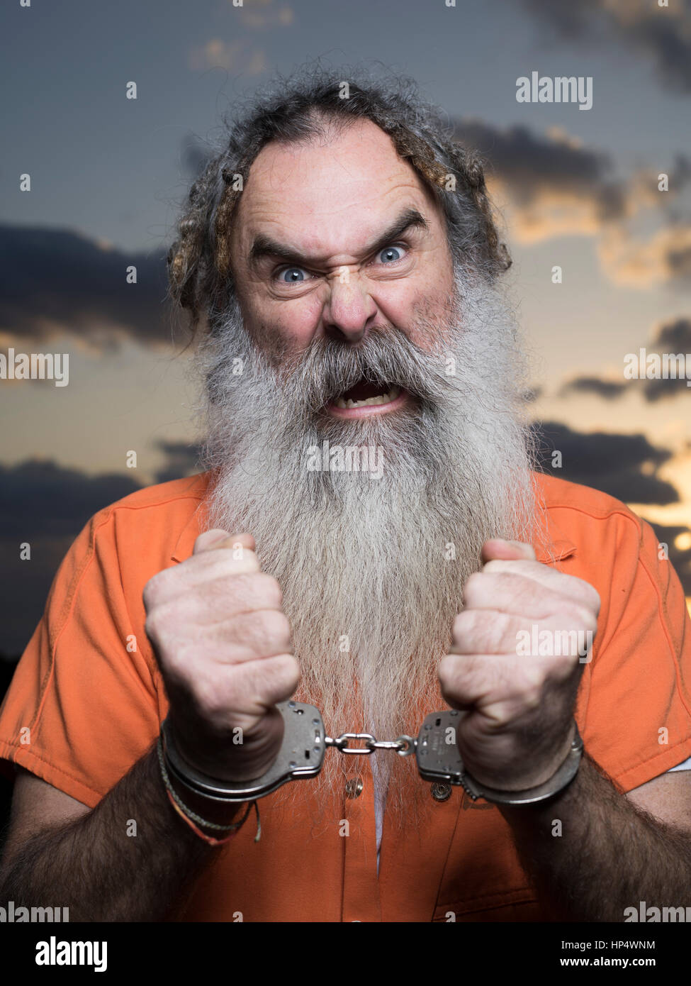Man with beard with prison orange jumpsuit - Stock Image