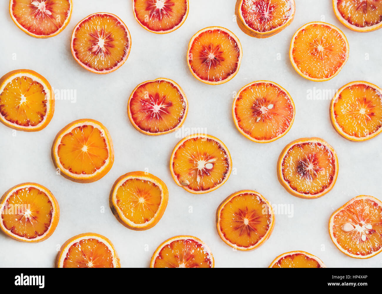 Natural fruit pattern concept. Fresh juicy blood orange slices over light marble table background, top view - Stock Image