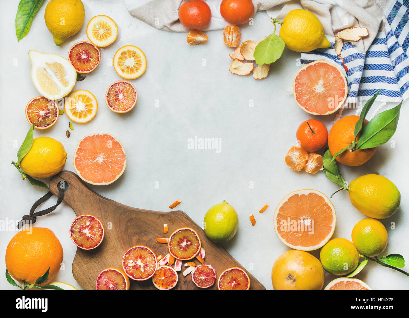 Natural fresh citrus fruits on wooden rustic board over grey marble table background, top view, copy space - Stock Image