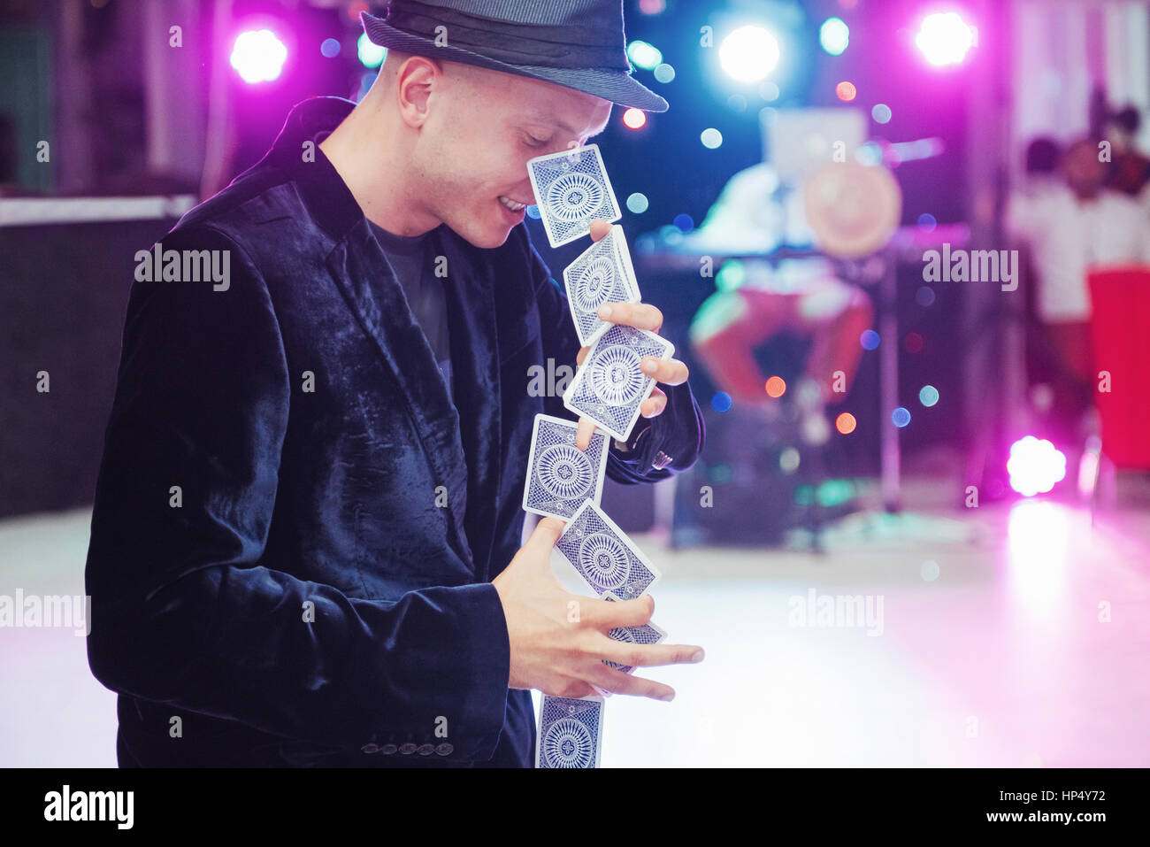 Portrait juggler magician is interesting black suit with cards i Stock Photo