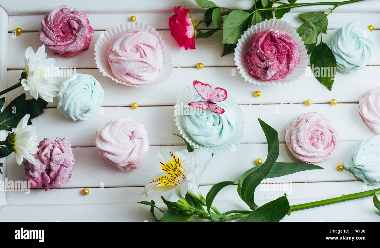 Rose marshmallows and beautiful flowers on a white background wo - Stock Image