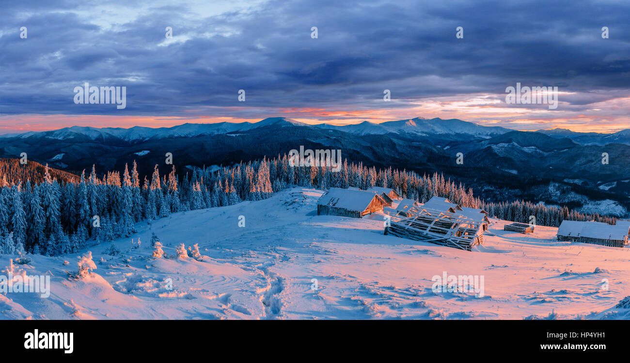 Fantastic sunset over snow-capped mountains and wooden chalets.  - Stock Image