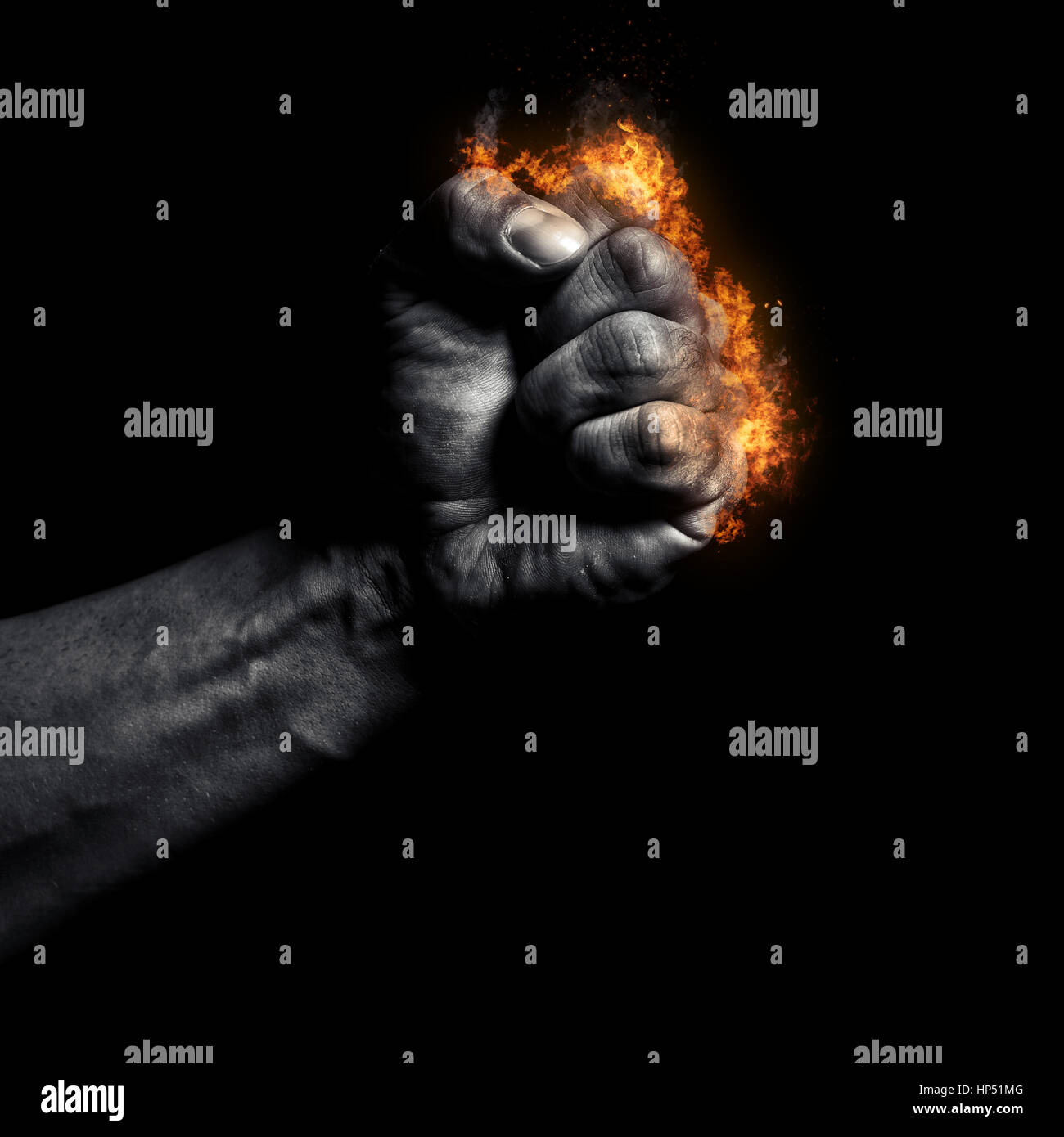 Burning man's clenched fist on a black background - Stock Image