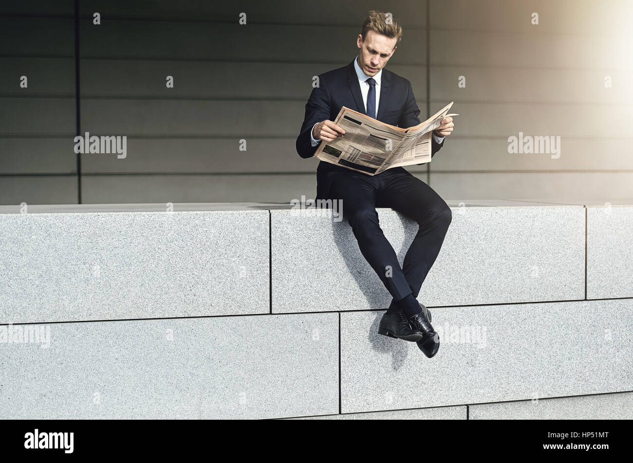 Cool businessman sits on a brick wall with newspaper - Stock Image
