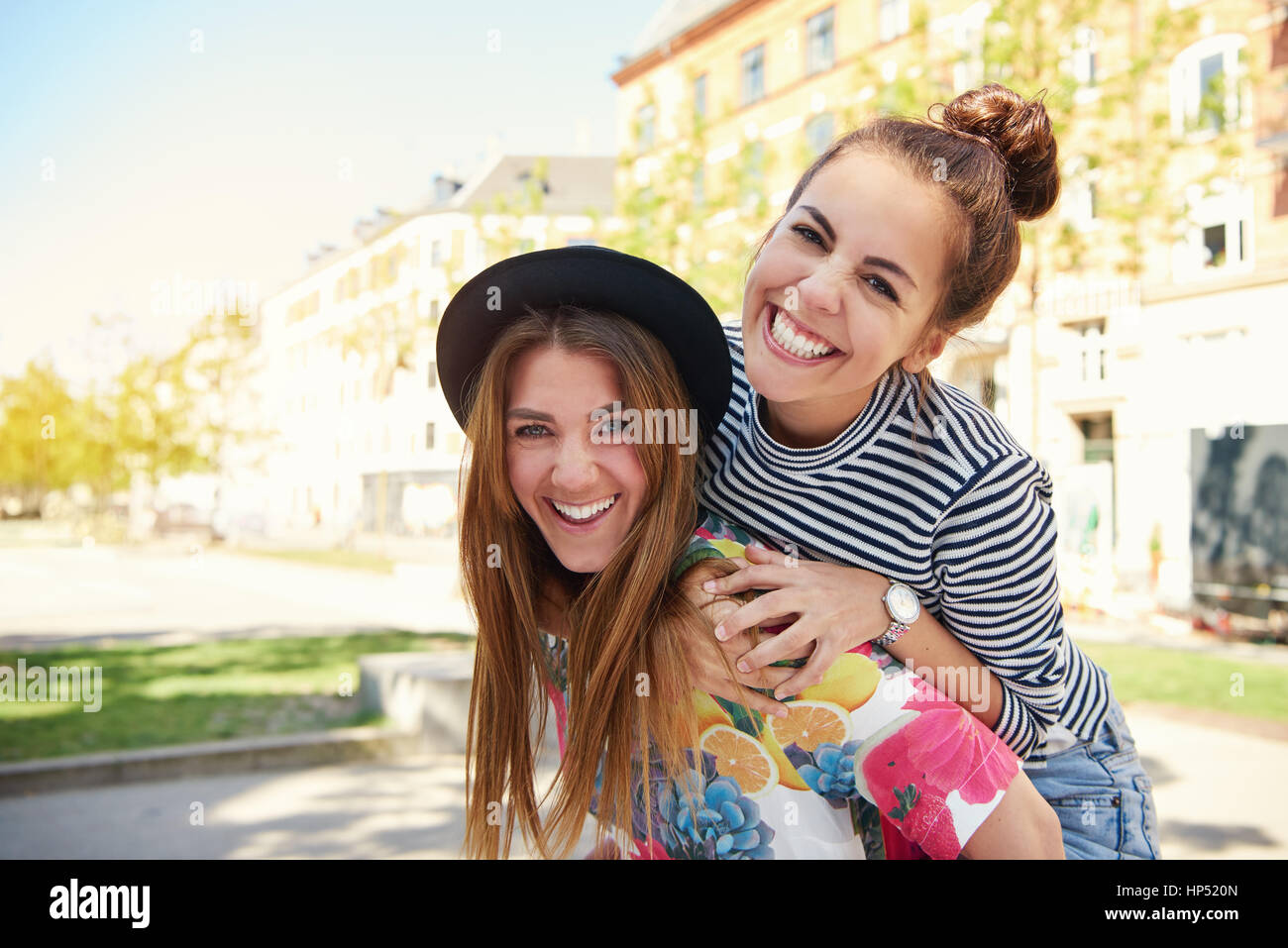 Two happy young women friends piggy backing in the shade of a tree in a quiet urban park grinning merrily at the - Stock Image
