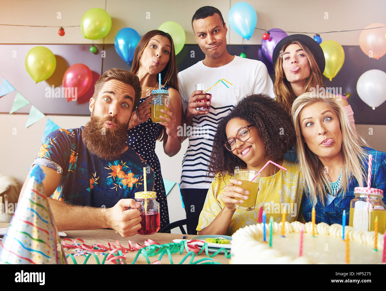 Goofy friends pulling silly faces while partying celebrating a birthday with festive party balloons and decorations - Stock Image