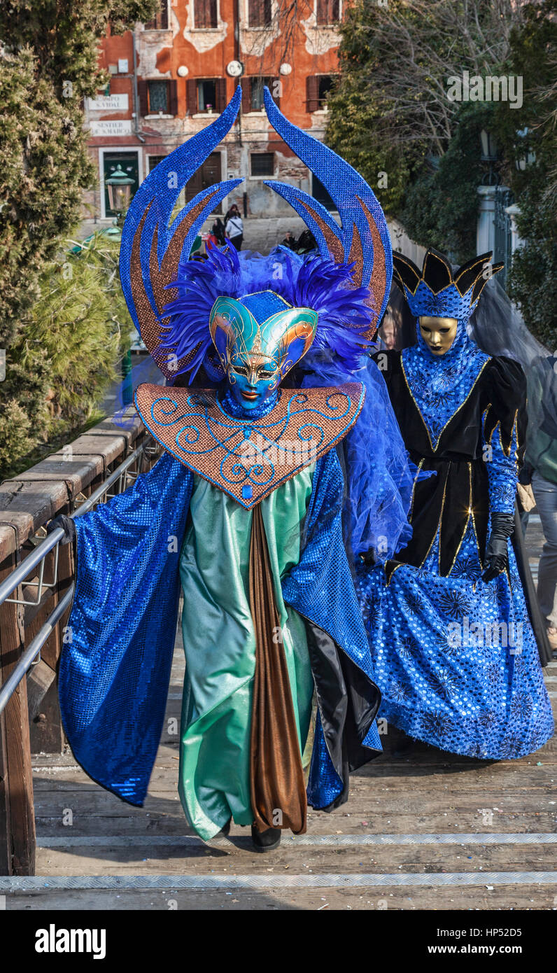 Venice,Italy-February 18, 2012: Two unidentified persons disguised in blue costumes walking on the Academia Bridge Stock Photo