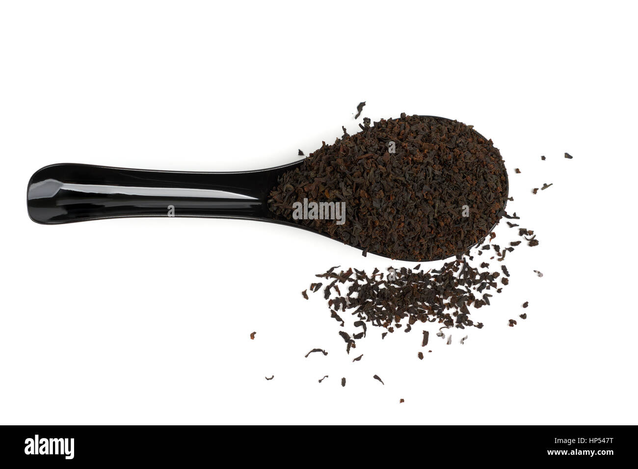 Black plastic spoon full of black tea isolated on white. Upper view. - Stock Image