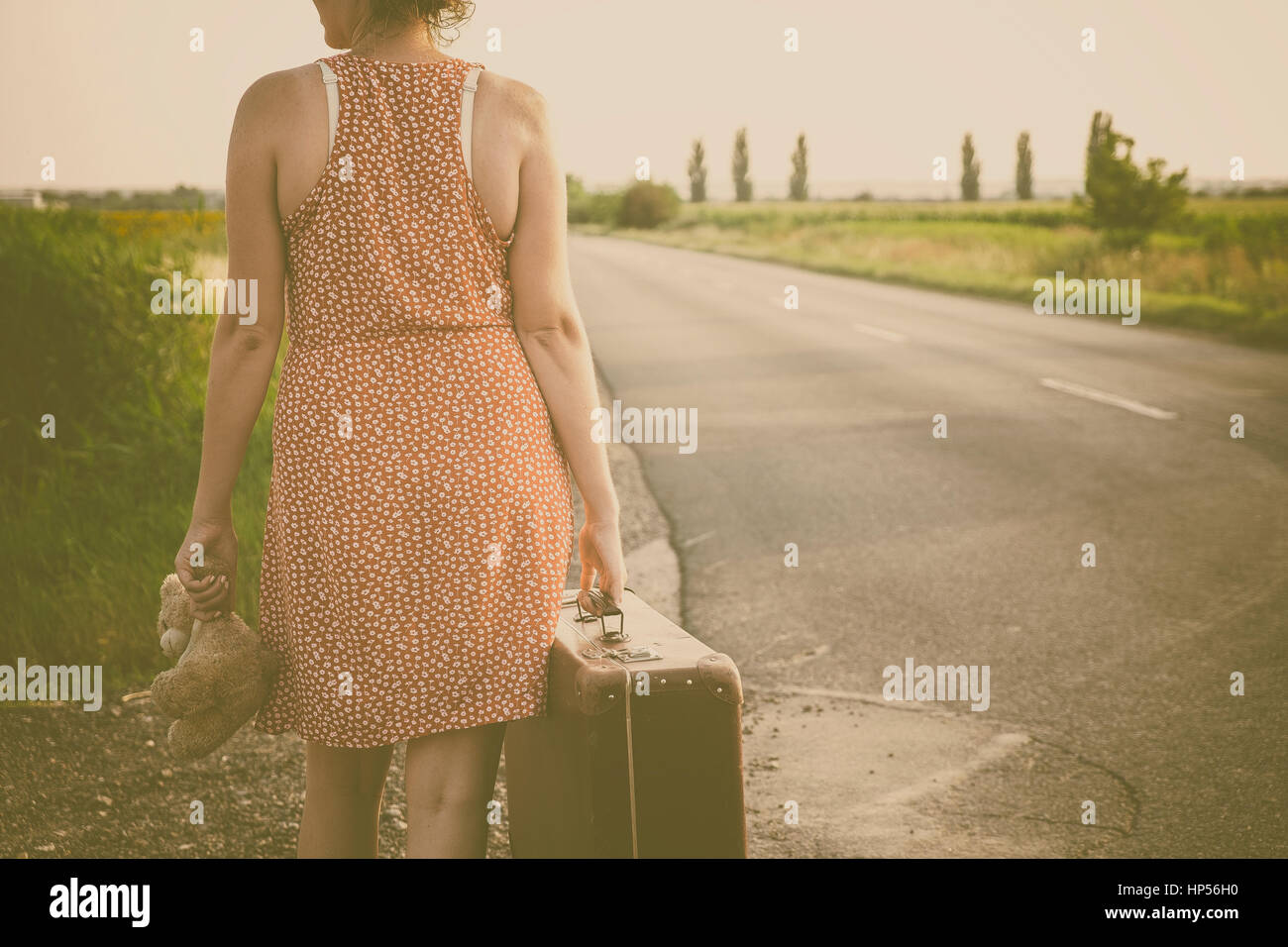 Woman on the road at summer sunset - Stock Image