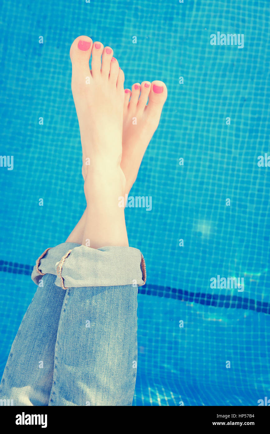 Woman legs rolled up jeans while enjoying by the swimming pool. Above POV.  Vacation concept