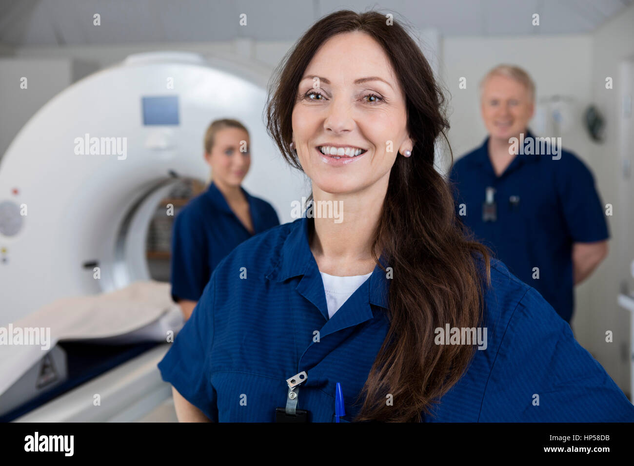 Smiling Female Radiologist With Colleagues Standing By MRI Machi - Stock Image