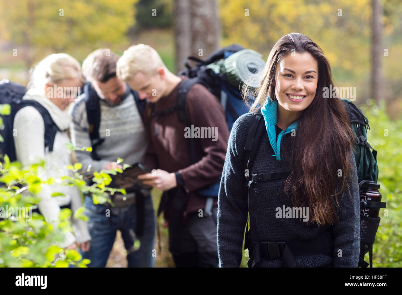 Happy Female Hiker With Friends Discussing In Background - Stock Image