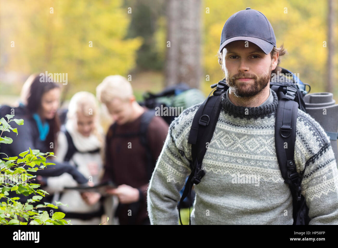 Confident Male Hiker With Friends Discussing In Background - Stock Image