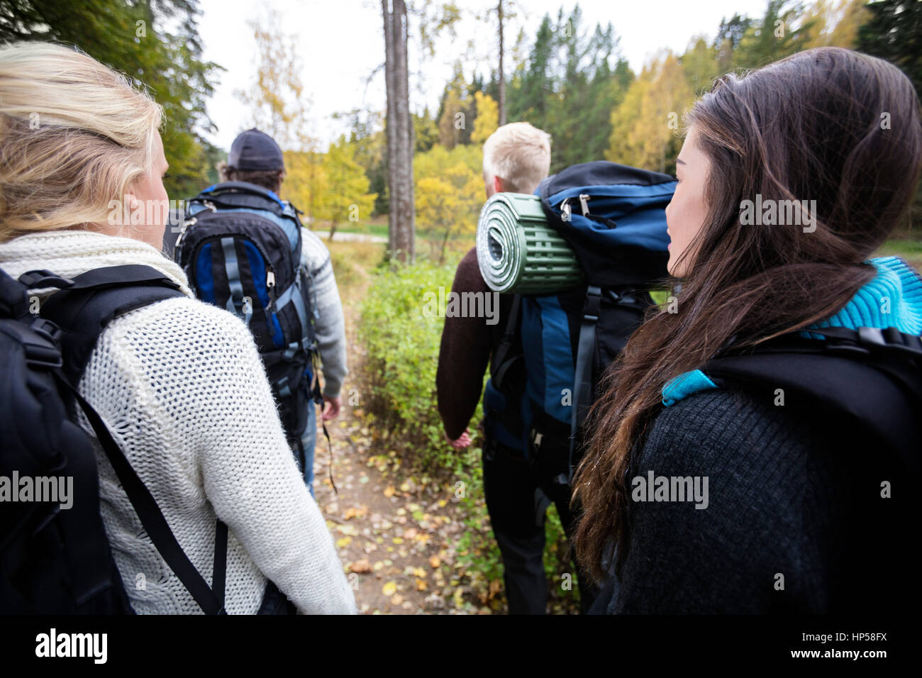 Hikers With Backpacks Walking On Forest Trail - Stock Image