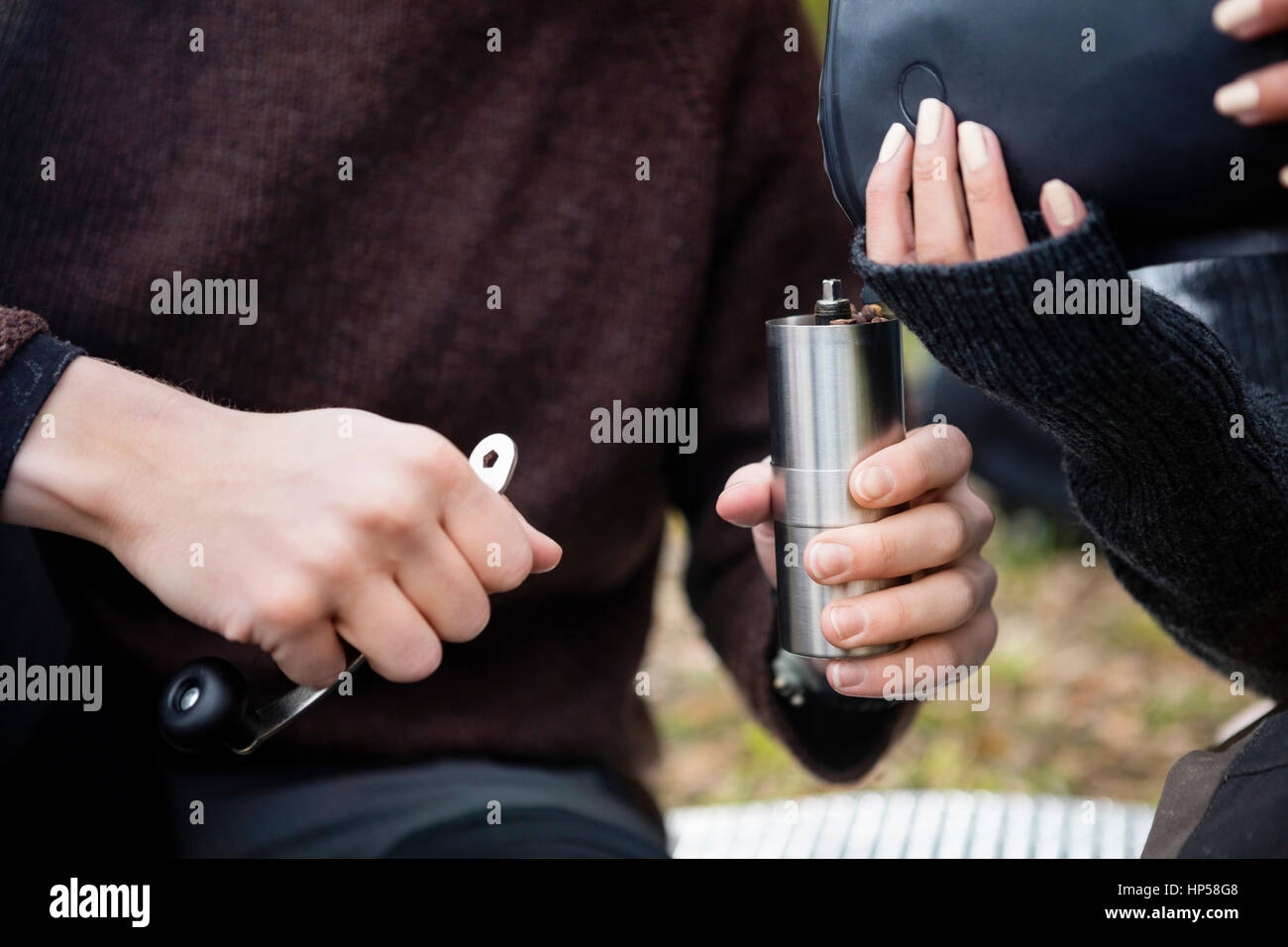 Woman Pouring Coffee Beans Into Grinder Held By Man - Stock Image