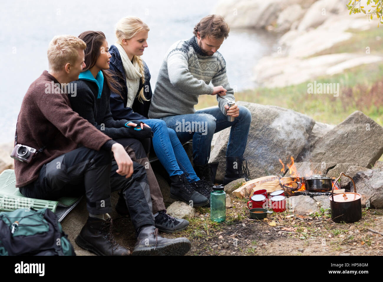 Friends Looking At Man Grinding Coffee At Campsite - Stock Image