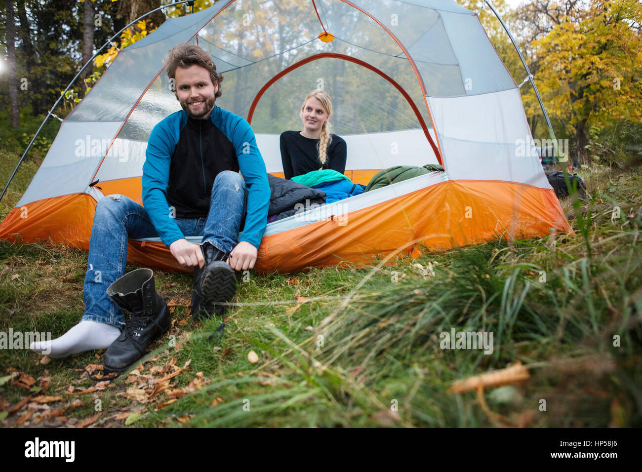 Man Wearing Boot While Woman Relaxing In Tent - Stock Image