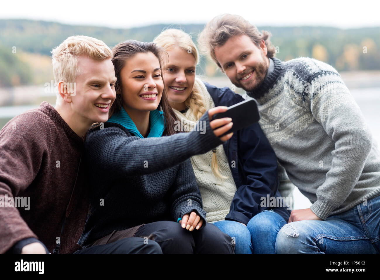 Friends Taking Selfie With Smartphone At Campsite - Stock Image