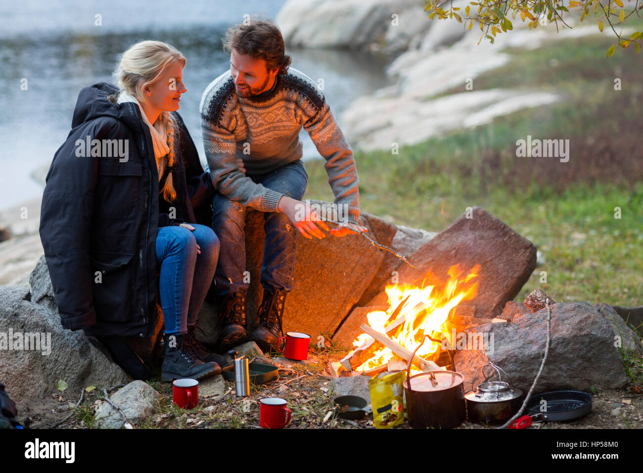 Couple Looking At Each Other White Sitting By Campfire Stock Photo