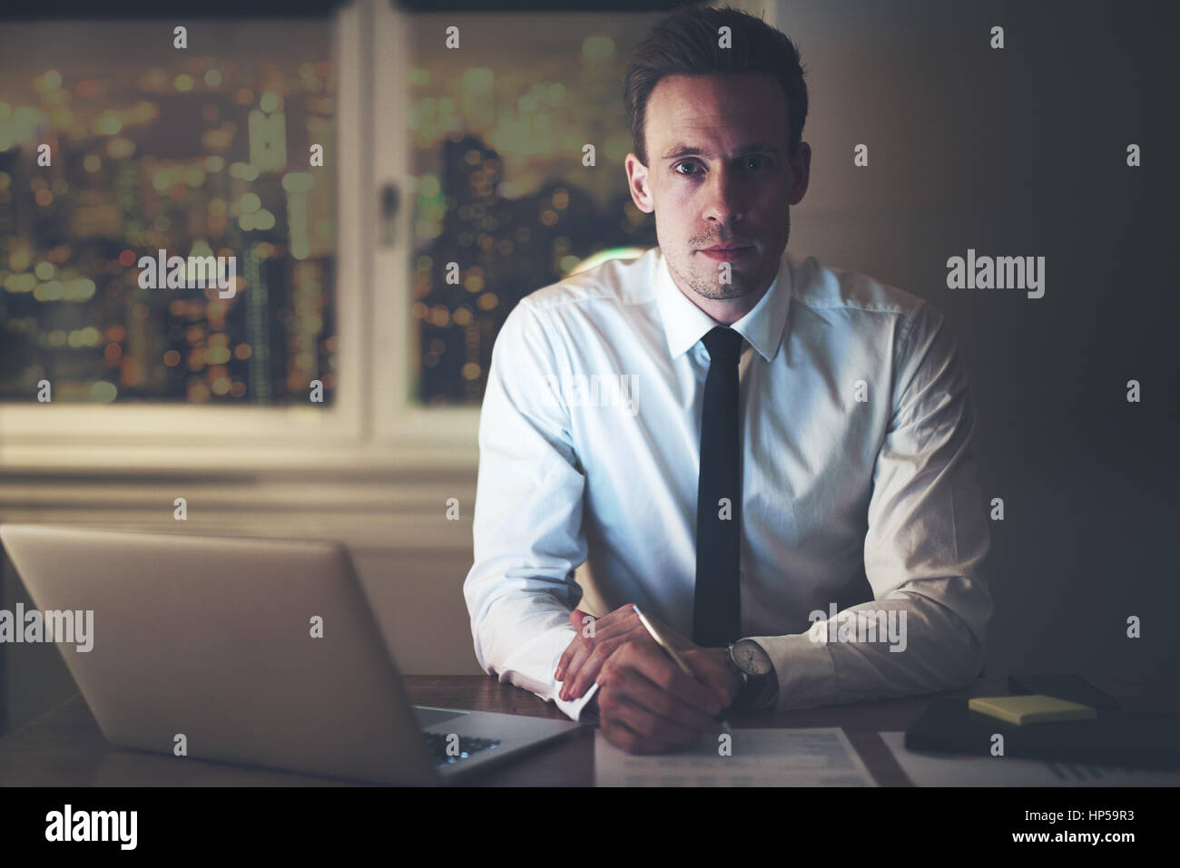 Serious businessman at office sitting at desk working, looking into camera, Classic business concept - Stock Image