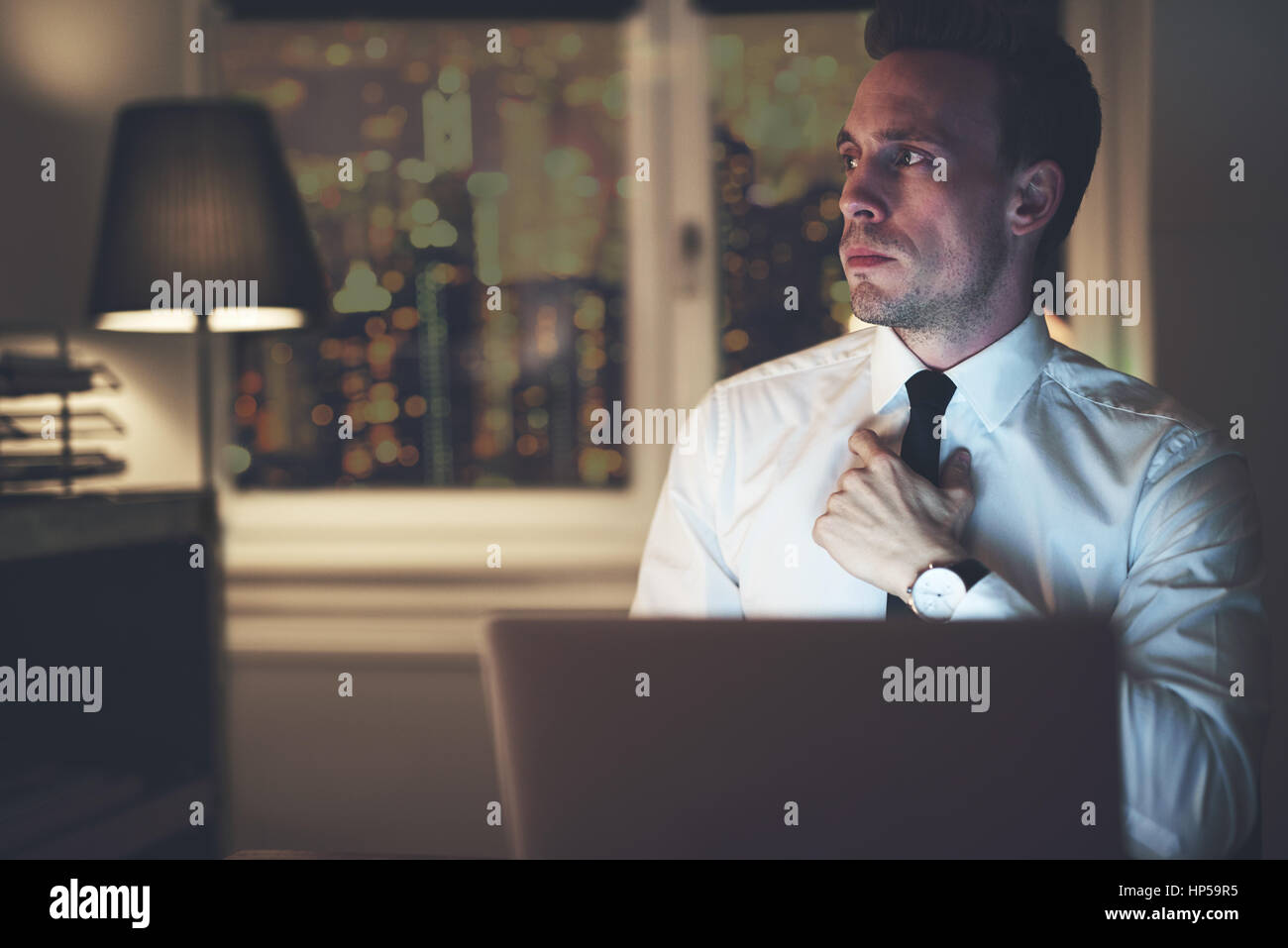 Serious businessman thinking sitting at office at night working overtime, solving a problem Stock Photo