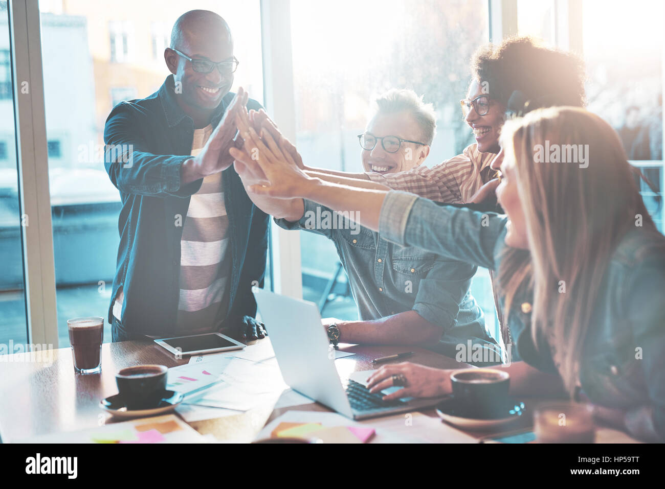 Happy young entrepreneurs in casual clothes at cafe table or in business office giving high fives to each other - Stock Image