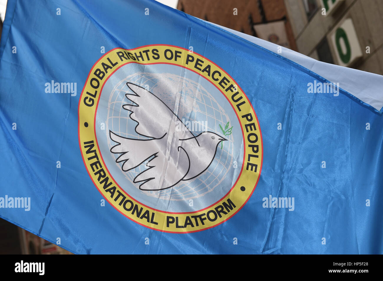 """Munich, Germany. 18th Feb, 2017. A flag with the letters """"Global Rights of Peaceful People - International Platform"""" Stock Photo"""